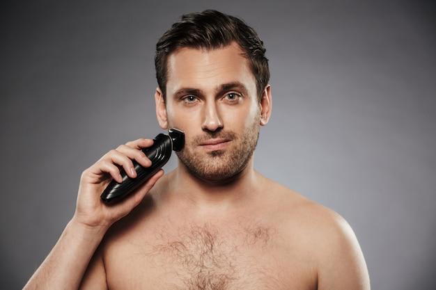 Foto de homem bonito, depilar o rosto com o barbeador elétrico, fazendo o procedimento de manhã no banheiro contra a parede cinza