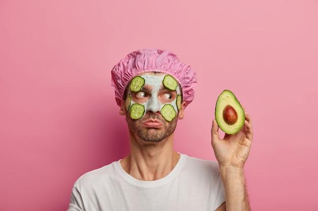 Foto de homem bonito fazendo tratamento facial de rejuvenescimento, segura abacate, aplica fatias de pepino frescas, usa touca de banho