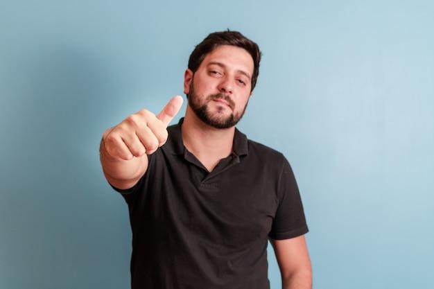 Foto de homem bonito sorrindo para a câmera com o polegar para cima