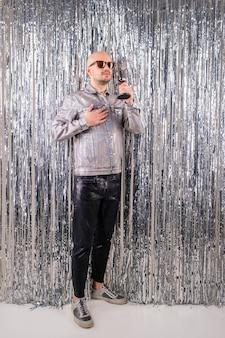 Foto de homem caucasiano bonito sem cabelo com óculos de sol pretos em uma camisa brilhante, calça de couro preta e tênis cinza canta em um pequeno microfone prateado