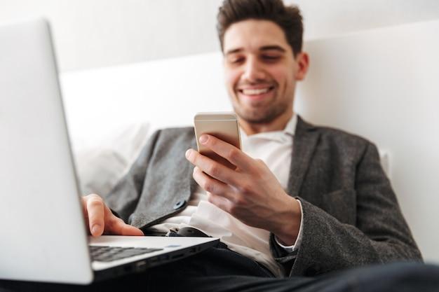 Foto de homem com barba em roupas profissionais desfrutando de ficar na cama, enquanto estiver usando o laptop e smartphone