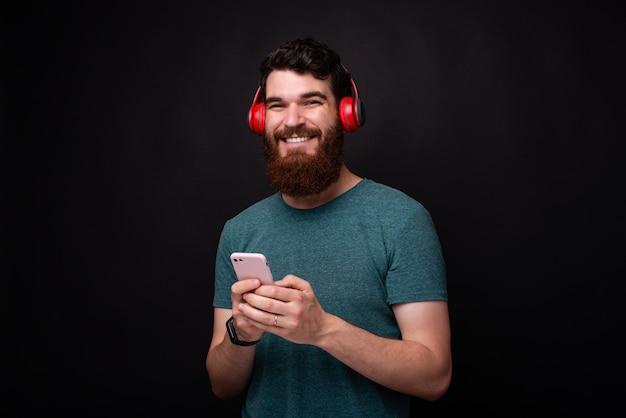Foto de homem com barba, olhando para a câmera e sorrindo, homem segurando o smartphone e usando fones de ouvido vermelhos