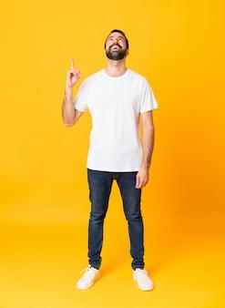 Foto de homem com barba sobre amarelo isolado apontando para cima e surpreso