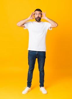 Foto de homem com barba sobre fundo amarelo isolado com expressão de surpresa