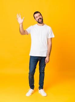 Foto de homem com barba sobre fundo amarelo isolado, saudando com a mão com expressão feliz