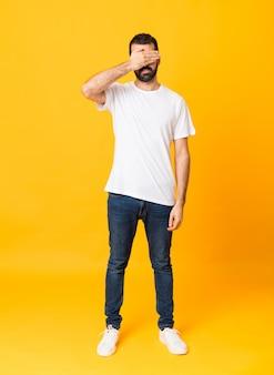Foto de homem com barba sobre olhos de cobertura amarela isolados pelas mãos. não quero ver algo