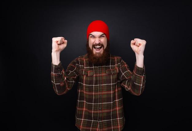 Foto de homem comemorando a vitória e gritando por cima da parede cinza, emoção, sucesso, gesto