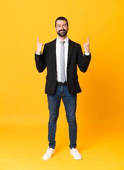 Foto de homem de negócios sobre amarelo isolado apontando uma ótima idéia
