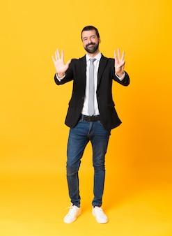 Foto de homem de negócios sobre amarelo isolado contando oito com os dedos
