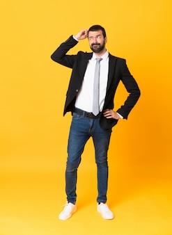 Foto de homem de negócios sobre amarelo isolado tendo dúvidas enquanto coça a cabeça