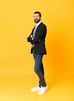 Foto de homem de negócios sobre fundo amarelo isolado com os braços cruzados e olhando para a frente