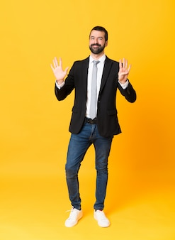 Foto de homem de negócios sobre fundo amarelo isolado, contando nove com os dedos