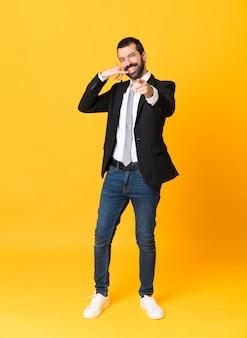 Foto de homem de negócios sobre fundo amarelo isolado, fazendo gesto de telefone e apontando a frente