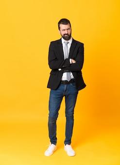 Foto de homem de negócios sobre fundo amarelo isolado, sentindo-se chateado