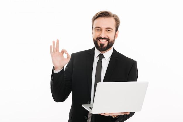 Foto de homem de sucesso em terno preto, sorrindo e mostrando sinal de ok, mantendo o notebook, isolado sobre a parede branca