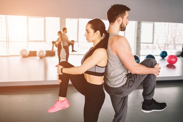Foto de homem e mulher em pé de costas e puxando uma perna. eles estão tentando manter o equilíbrio dos corpos por um lado.