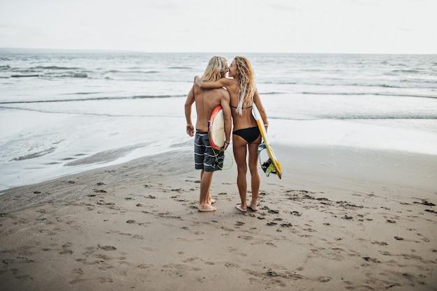 Foto de homem e mulher em trajes de banho segurando pranchas de surf contra o mar