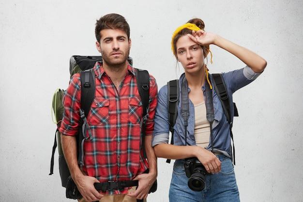 Foto de homem e mulher frustrados e exaustos, de aparência européia, carregando mochilas nos ombros, sentindo-se cansados e desgastados depois de passar uma noite sem dormir na estrada enquanto viajam de carona
