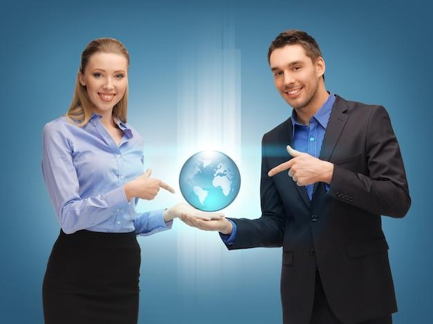 Foto de homem e mulher mostrando o globo terrestre nas palmas das mãos