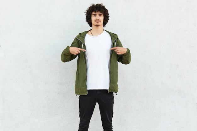 Foto de homem encaracolado aponta para camiseta branca, mostra espaço livre para o seu anúncio, logotipo ou conteúdo promocional, posa sobre muro de concreto
