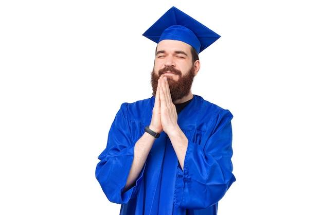 Foto de homem estudante solteiro e chapéu de formatura rezando