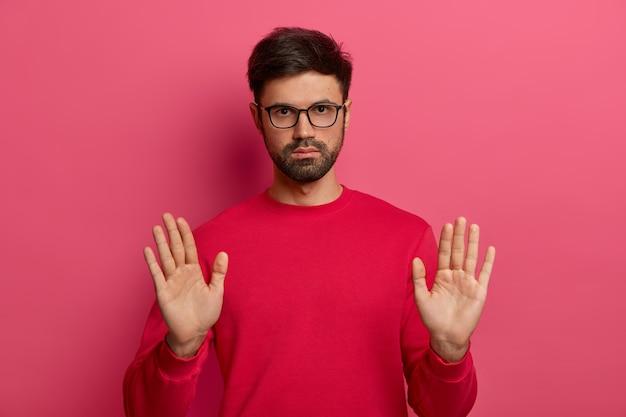 Foto de homem europeu com a barba por fazer faz gesto de pare, segure sinal, puxa as palmas das mãos, olha sério, tem expressão determinada, pede para se acalmar, usa suéter vermelho, óculos.