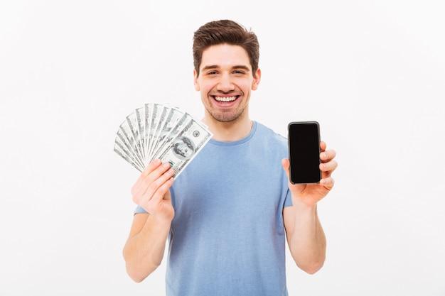 Foto de homem feliz na camiseta casual, segurando o leque de dinheiro em notas de dólar e celular nas mãos, isolado sobre a parede branca
