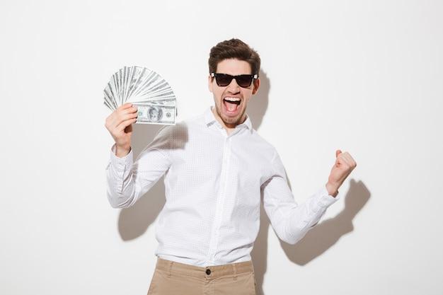 Foto de homem feliz vencedor de camisa e óculos de sol, gritando e segurando leque de dinheiro em notas de dólar com o punho cerrado, isolado sobre a parede branca com sombra
