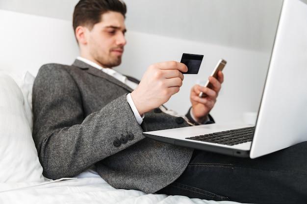 Foto de homem inteligente de terno, deitada na cama, enquanto paga on-line com cartão de crédito usando o laptop e telefone celular