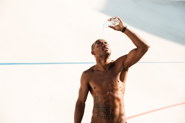 Foto de homem jovem esportes africanos, derramando água na cabeça