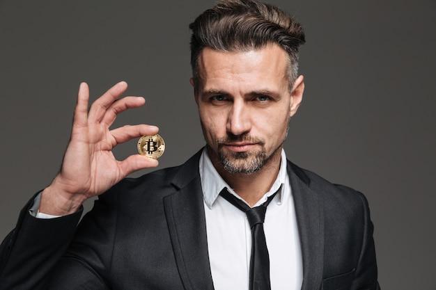 Foto de homem maduro bem sucedido com cabelo castanho de terno e gravata demonstrando bitcoin dourado na câmera, isolada sobre cinza escuro