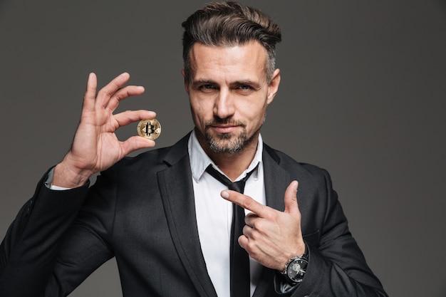 Foto de homem maduro bem sucedido com cabelo castanho em publicidade de terno e gravata e dedo apontando no bitcoin dourado, isolado sobre cinza escuro