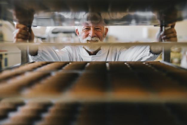 Foto de homem maduro profissional padeiro masculino em uniforme de trabalho branco, olhando para a câmera. de pé na frente das prateleiras cheias de biscoitos recém-assados.