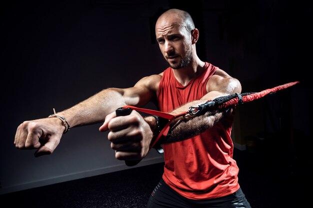 Foto de homem musculoso durante o treino com cintas de suspensão trx no estúdio escuro.