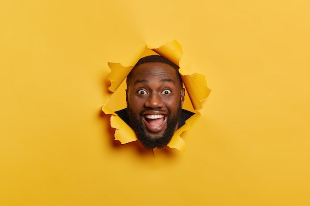Foto de homem negro feliz com expressão facial satisfeita, cerdas escuras, se diverte dentro de casa, mantém a cabeça no buraco do papel rasgado, ri e olha para a câmera, isolada sobre fundo amarelo.