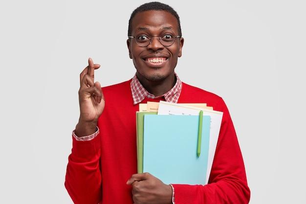 Foto de homem negro feliz cruzando os dedos para dar sorte, carregando livros didáticos, com sorriso cheio de dentes, vestido com roupas vermelhas