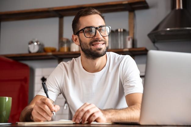 Foto de homem positivo na casa dos 30 anos usando óculos e escrevendo anotações enquanto usa um laptop prateado na mesa da cozinha