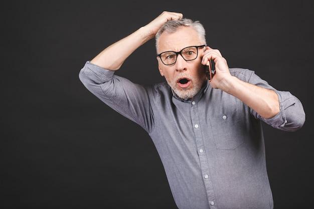 Foto de homem sênior chocado com óculos ofegante boca de abertura e surpresa segurando o smartphone recebendo más notícias olhando preocupado e atordoado com a câmera isolada sobre fundo preto.
