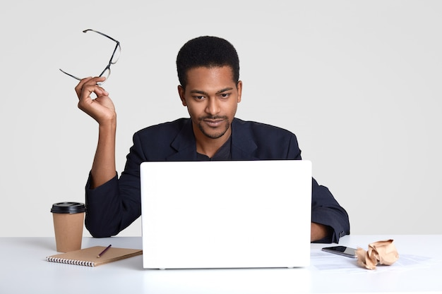 Foto de homem sério de pele escura trabalha como freelancer, mantém os óculos nas mãos, lê notícias no site da internet, focada no monitor do laptop, usa terno formal, senta-se no espaço de coworking sobre parede branca