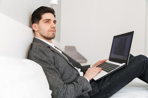 Foto de homem sério inteligente em roupas profissionais, olhando de lado com a vista pensativa, enquanto estava deitado na cama e trabalhando no laptop
