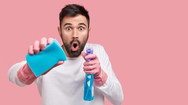 Foto de homem surpreso com a boca aberta, olhando em choque, carregando esponja e spray de limpeza, olhando estupefato, vestindo roupas brancas