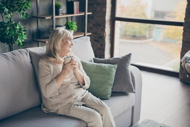 Foto de incrível loira adorável vovó idosa caseira bom humor bebendo bebida quente parecendo sonhadora para a janela memórias sentado confortável sofá divã sala de estar dentro de casa