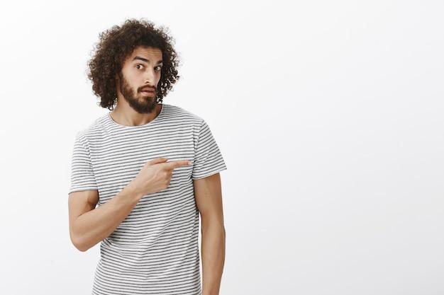 Foto de indor de um cara hispânico atraente duvidoso desavisado, com barba e penteado afro, apontando para a direita com o dedo indicador