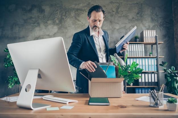 Foto de infeliz despedido trabalhador maduro gerente perdedor perdeu o emprego crise falência embalagem pertences caixa pessoal caixa grande monitor mesa escritório colisão financeira área de trabalho dentro de casa