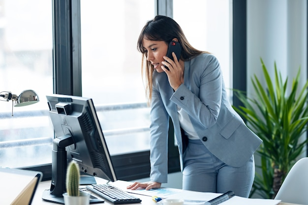 Foto de inteligente jovem empresária falando com o celular enquanto trabalhava com o computador no espaço de trabalho moderno.