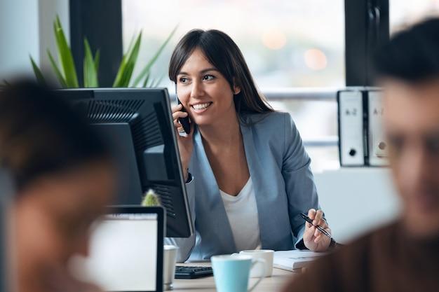 Foto de inteligente jovem empresária falando com o celular enquanto trabalhava com o computador, olhando pela janela no espaço de trabalho moderno.