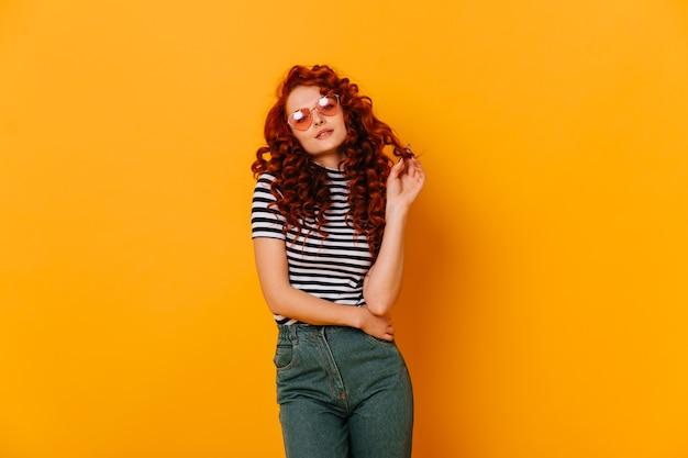 Foto de jovem adolescente coquete em jeans de mães e camiseta listrada, tocando seus cachos no espaço laranja.