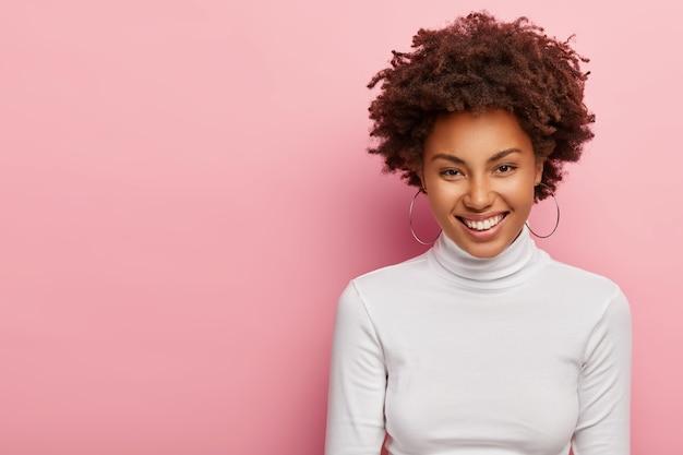 Foto de jovem adorável com cabelos afro crespos, sorri gentilmente, usa brincos e blusão branco, satisfeita com a obtenção de um novo emprego, conversa agradável com o colega, fica em pé sobre a parede rosa