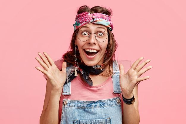 Foto de jovem alegre com expressão feliz, gesticula com as mãos, tem expressão radiante, não espera ver algo inacreditável, usa óculos e bandana, isolada no rosa