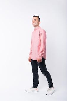 Foto de jovem alegre de camisa vermelha andando sobre fundo branco.